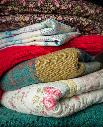 Pile of different coloured and textured quilts